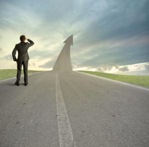 """Die """"road to success"""" ist lang. Ein Mann im Anzug blick in die Ferne."""